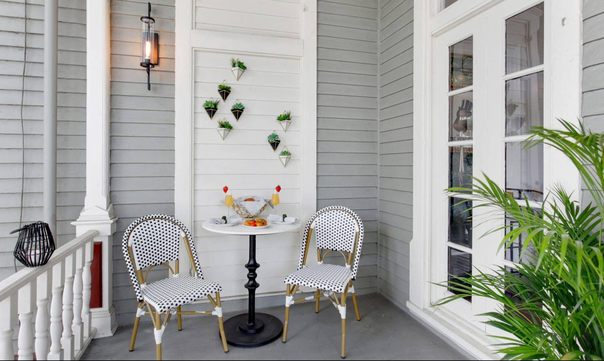 Two chairs sit side-by-side with a table in between on the front porch of an Heirloom Savannah home. Cocktails are on the table and a plant wall hangs behind the tableau.