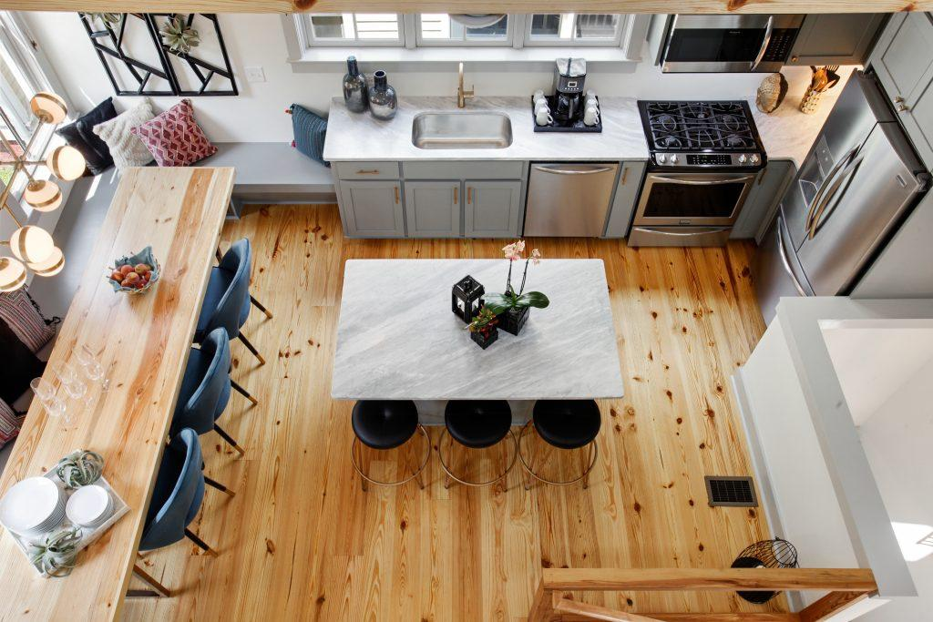 Aerial shot of an Heirloom kitchen in Savannah, GA. When we design vacation rentals for big groups, we make sure each home is special. Here, warm wood tones throughout immediately grab the eye, from the flooring, table, and ceiling beams. A dining table lines the left side of the photo, a breakfast bar island is in the center of the photo, and the sink and appliances go from the center-back of the image wrapping around the back along the right side.