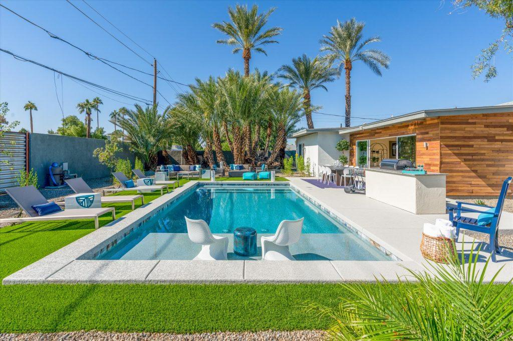 The sun shines down on a glittering, turquoise pool in the backyard of an Heirloom luxury home in Phoenix, AZ. Loungers line the pool as does a grill and outdoor kitchen, and palm trees rise in the background of the photo over the fire pit. The perfect vacation rental for big groups.